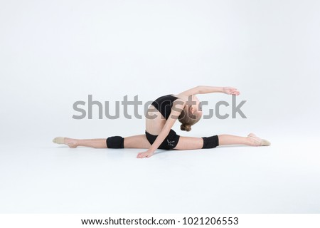 Rhythmic gymnastics caucasian blonde girl in black suite performing athlete exercises showing flexibility and stretching abilities acrobat balance on white background isolated
