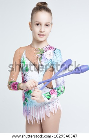 Rhythmic gymnastics caucasian blonde girl in dress for shows with clubs performing flexibility and acrobat balance on white background isolated