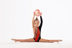 Rhythmic gymnastics. Girl gymnast sitting on a white background in twine with a ball. Children and sports, healthy lifestyle.