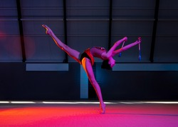 Rhythmic gymnastics. Solo performance. Young female rhythmic gymnast practicing isolated over colored background in neon light. Concept of motion, sport life, action, competition. Copy space for ad.