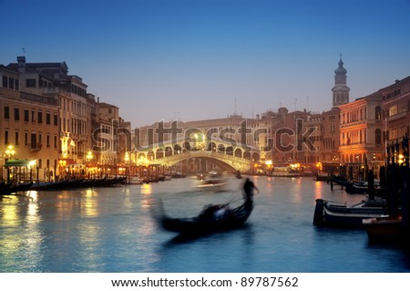 Rialto Bridge and gondolas at a foggy autumn evening in Venice.