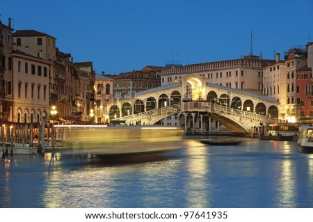 Rialto Bridge and motion blured water bus at Grand Canal in Venice - Italy