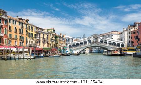 Rialto Bridge over the Grand Canal in Venice, Italy. Famous Rialto Bridge (Ponte di Rialto) is one of the main travel attractions of Venice. Historical architecture and cityscape of Venice in summer. #1011554041