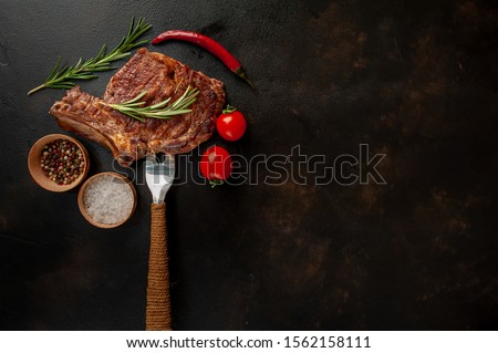 Rib eye beef steak on a fork with spices, tomatoes and red pepper