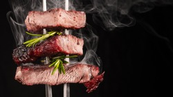 Rib eye beef steak with rosemary. Grilled ribeye beef steak on a fork. Black background. Food photographer.