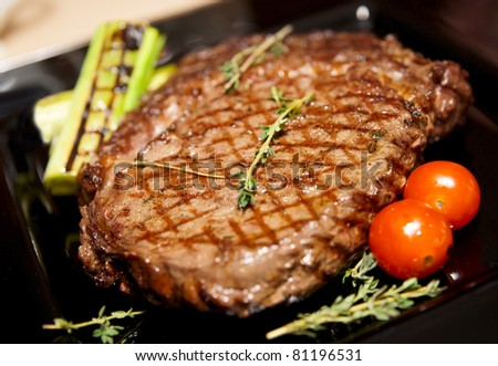 Rib eye steak served on black plate with herbs and grilled vegetables