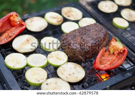 Rib eye steak with vegetables on bbq grill