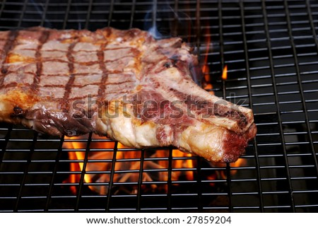 Rib steak on the barbecue with smoke and flames