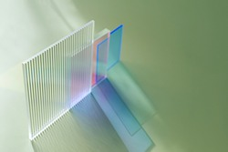 Ribbed and multicolored glass on a green background. The light travels through different acrylic sheets