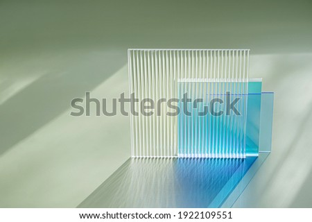 Ribbed and multicolored glass on a green background. The light travels through different acrylic sheets   Foto stock ©