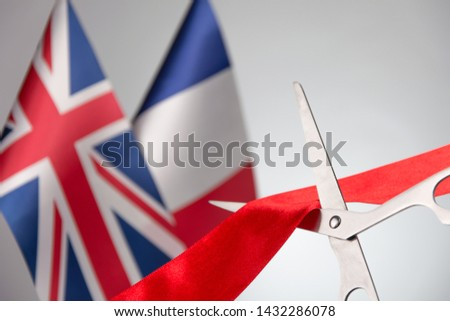 Ribbon cutting ceremony. Scissors cut red ribbon. France flag and Union Jack bluered on the background. concept  international agreements cooperation #1432286078