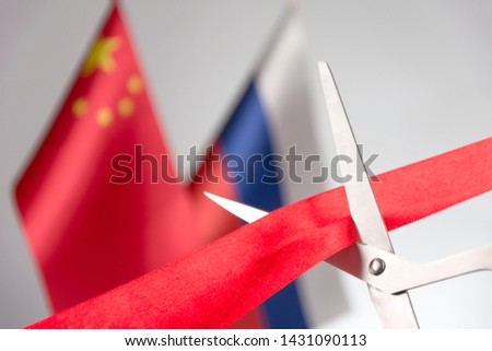 Ribbon cutting ceremony. Scissors cut red ribbon. Russian and China flag bluered on the background. Concept international agreements #1431090113