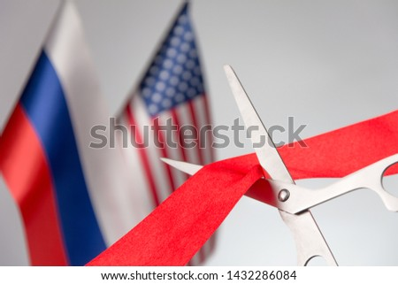Ribbon cutting ceremony. Scissors cut red ribbon. Russian and USA flag bluered on the background. reaching agreements concept #1432286084