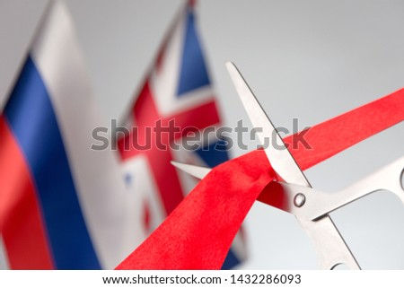 Ribbon cutting ceremony. Scissors cut red ribbon. Russian flag Union Jack bluered on the background. Concept international agreements #1432286093