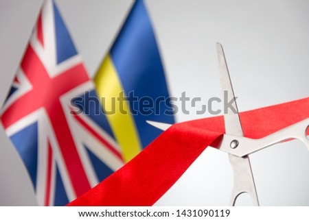 Ribbon cutting ceremony. Scissors cut red ribbon. Ukraine and Union Jack bluered on the background. reaching agreements, interstate cooperation #1431090119