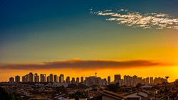 Ribeirao Preto city at sunset - Sao Paulo, Brazil. Buildings located on the avenue Joao Fiusa in Ribeirao Preto on the horizon at sunset with blue sky with some clouds.