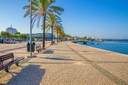 Ribeirinha de Portimao town, cobblestone embankment promenade of Arade River in city centre with palm trees and benches, blue sky background, Faro district, Algarve region, Portugal