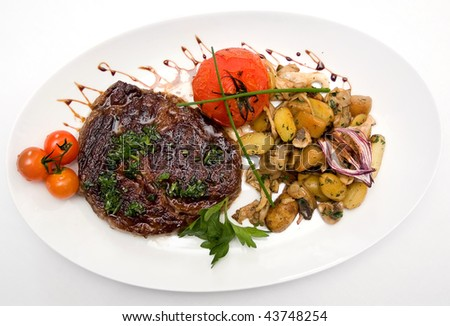 Ribeye steak from marble beef, roasted tomatoes and mini-potatoes with mushroom - stock photo