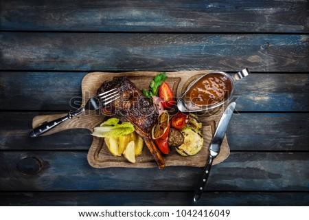 Ribeye steak on bone served with sauce Jack Daniels