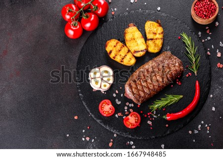 Ribeye steak with potatoes, onions and cherry tomatoes. Juicy steak with flavored butter