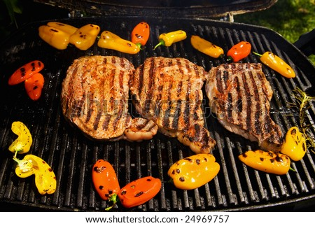 ribeye steaks cook on the bar-b-que grill with baby bell peppers