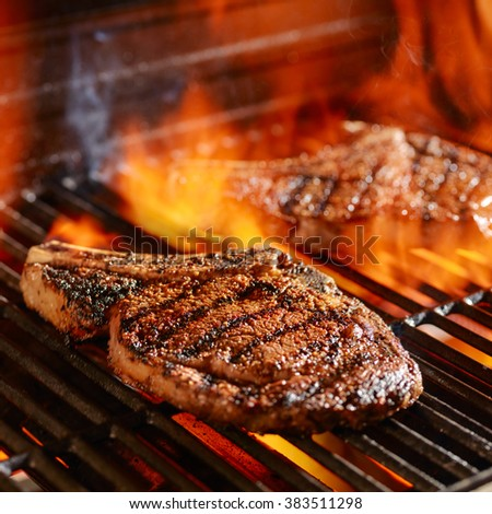 ribeye steaks on the grill over the open flame