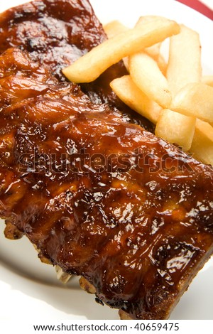 Ribs with smoky spicy sauce accompanied by french fries