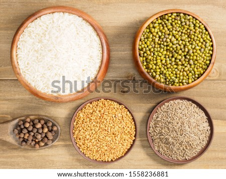 Rice, allspice, fenugreek, cumin, mung bean on brown wooden background. Indian cuisine, ayurveda, naturopathy, modern apothecary concept #1558236881