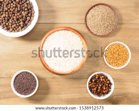 Rice, allspice, mustard seeds, fenugreek, cumin, cloves on brown wooden background. Indian cuisine, ayurveda, naturopathy, modern apothecary concept #1538912573
