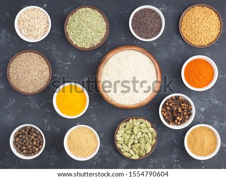 Rice, allspice, pepper chili, fenugreek, cloves, turmeric, masala, dry ginger, fennel, green cardamom, mustard seeds in bowls on black concrete background with copy space #1554790604