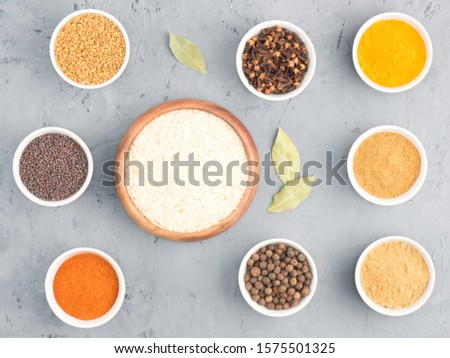 Rice, allspice, pepper chili, fenugreek, cloves, turmeric, masala, dry ginger, mustard seeds in bowls on black concrete background with copy space. Indian cuisine, ayurveda, naturopathy concept #1575501325