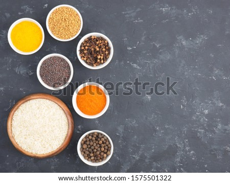 Rice, allspice, pepper chili, fenugreek, cloves, turmeric, mustard seeds in white bowls on black concrete background with copy space. Indian cuisine, ayurveda, naturopathy concept #1575501322