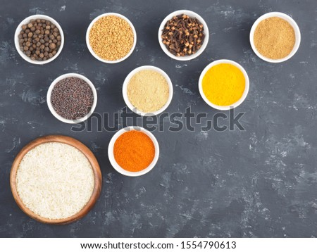 Rice, allspice, pepper chili, masala, fenugreek, cloves, turmeric, mustard seeds in white bowls on black concrete background with copy space. Indian cuisine, ayurveda, naturopathy concept #1554790613