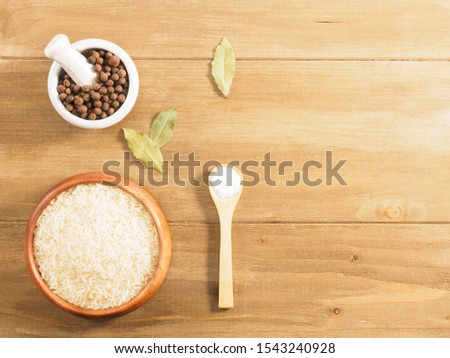 Rice, allspice, salt on brown wooden background. Indian cuisine, ayurveda, naturopathy, modern apothecary concept #1543240928