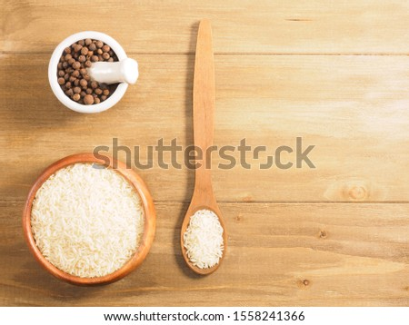 Rice and allspice on brown wooden background. Indian cuisine, ayurveda, naturopathy, modern apothecary concept #1558241366