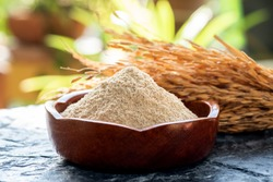 Rice bran and rice seeds on a natural background.