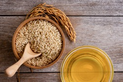 Rice bran oil extract with paddy and brown rice on wood table background. Top view. Flat lay.