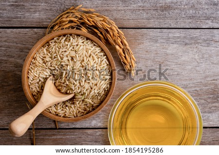Rice bran oil extract with paddy and brown rice on wood table background. Top view. Flat lay. Stock photo ©