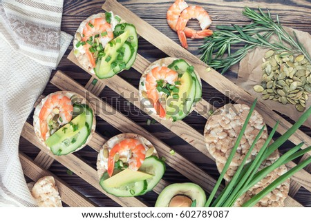 Rice cakes with sliced avocado cucumber shrimp and cream cheese.  Fresh parsley and rosemary. Vegetarian, vegan concept. Shallow depth of field. Coloring and processing photo #602789087