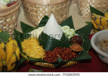 rice cone, fried beans, fried eggs and other dishes in a bamboo tray