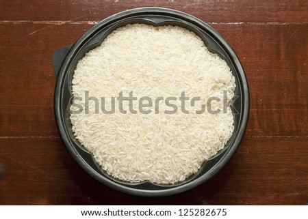 Rice grain uncooked in flower shape bowl on wooden board