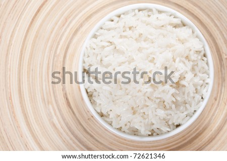 Rice in a bowl on a bamboo plate. Concept of the importance of rice