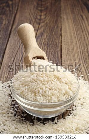 Rice in a glass bowl with a wooden spoon on the table