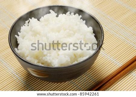 rice in black round bowl with chopsticks