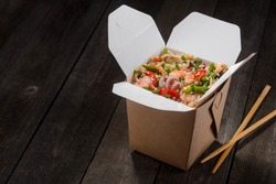 Rice in box and chopsticks on wooden table. Delicious blend of rice, seafood and vegetables is result of Chinese recipe. Asian food delivery.