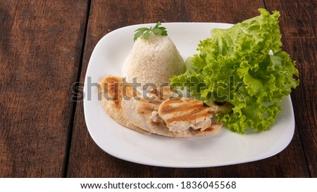 Rice, lettuce and grilled chicken on a white plate, on wooden surface, gray background, selective focus. Сток-фото ©