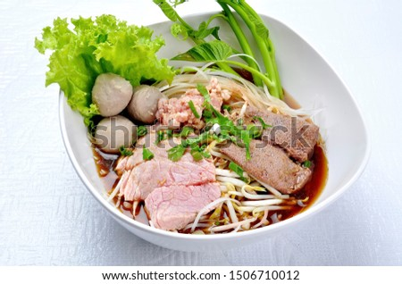 Rice noodle soup with beef ball and stewed beef and sprouts on white table. Beef noodle with vegetable and nature ingredient. Asian food. Noodles with beef and beff balls with soup Thai style.