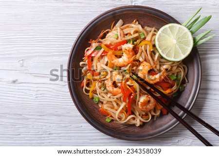Rice noodles with shrimps and vegetables close-up on the table. top view of a horizontal #234358039