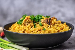 Rice pilaf with meat carrot and onion on grey background. Side view.