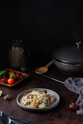 Rice pilaf with meat on a plate on a brown wooden table, with kitchen utensils, cauldron, peppers, garlic. Home atmosphere. Nearby spoons, in the background a jar of rice